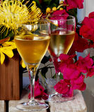Cheers. Image of two wine glasses with red and yellow flowers on a teak table Stock Photography