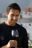 Cheers. Young man holding a cup of wine Royalty Free Stock Photo