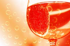 Cheers. Droplets and bubbles of sparkling water or wine with cherry splash in wine glass. Dominant orange red colors Royalty Free Stock Photo