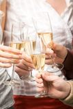 Cheers!. Close-up of friends hands holding glasses with champagne and making cheers Stock Photos