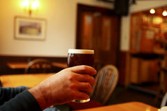 Cheers with ale. Man lifts a pint of ale in the pub Stock Photography