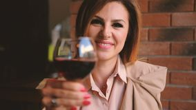 Cheers attractive business woman clink glass wine. Cheers! Attractive business woman at dinner clinking a glass of red wine to camera stock video footage