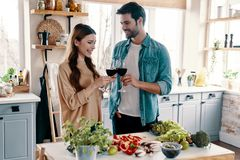 Cheers!. Beautiful young couple cooking dinner and drinking wine while standing in the kitchen at home stock photos