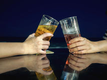 Cheers beer alcohol celebration making a toast at the beach Stock Photos