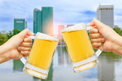 Cheers beer for celebration in your business success. Cheers beer for celebration in your business success with burred city background Royalty Free Stock Photography
