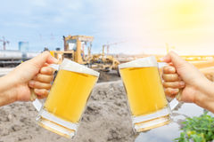 Cheers beer for celebration in your business success. Cheers beer for celebration in your business success with burred construction site background Stock Photos