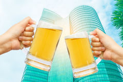 Cheers beer for celebration in your business success. Cheers beer for celebration in your business success with burred modern building background Royalty Free Stock Photography