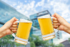 Cheers beer for celebration in your success with burred building background. Royalty Free Stock Photography