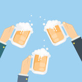 Cheers with beer. Hands hold beer glasses with foam and splash. Idea of celebration Stock Photography
