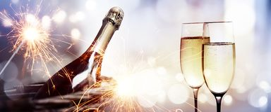 Cheers with a bottle of champagne for a new year. On sparkeling background and bright bokeh royalty free stock photos