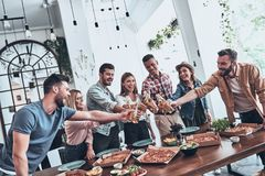 Cheers!. Group of young people in casual wear toasting each other and smiling while having a dinner party stock photography