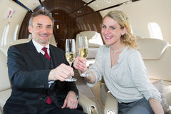 Cheers clink glasses business team in a corporate jet drinking c royalty free stock photo