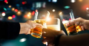 Cheers clinking of friends with beer drink in party night. Cheers clinking of friends with beer drink in party night after work on colorful blur background stock image