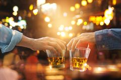 Cheers clinking of friends with bourbon whisky drink in party. Night after work on colorful background stock image