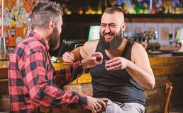 Cheers concept. Hipster brutal bearded man drinking alcohol with friend at bar counter. Men drunk relaxing at pub having. Cheers concept. Hipster brutal bearded stock image
