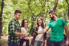 Cheers! Four happy friends, clinking their bottles of beer in a. Wood in a campsite, sunny nice day, green trees background Royalty Free Stock Images