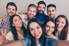Cheers! Funky mood. Close up of an eight excited friend`s selfie. Taken by brunette girl. Young people enjoy their company, smile, have fun royalty free stock photos