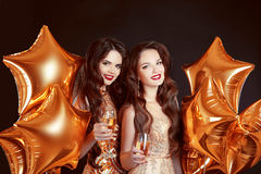 Cheers glasses, ladies have new year party celebration over part. Y golden stars balloons  on black background. Elegant two women in golden dresses Stock Images