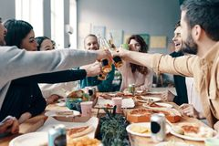 Cheers!. Group of young people in casual wear toasting each other and smiling while having a dinner party indoors royalty free stock images