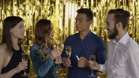 Cheers! 4 happy cheerful people at a party. The guys congratulate each other and drink champagne. A group of laughing. People of mixed race on a gold background stock video footage