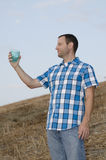 Cheers! Man holding plastic cup. Man looking out on a hill side while holding a cup with his arm extended wearing a plaid shirt Royalty Free Stock Images