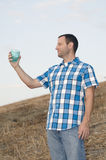 Cheers! Man holding plastic cup. Man looking out on a hill side while holding a cup with his arm extended wearing a plaid shirt Royalty Free Stock Photos