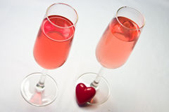 Cheers my love. Two stylish glasses with pink wine and a heart Stock Photography