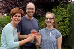 Cheers. Parents and daughter drinking nonalcoholic  coctails at a garden party Stock Image
