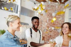Cheers of party. Intercultural group of young friends clinking with flutes of champagne at party Royalty Free Stock Photos