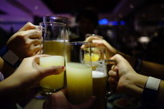 Cheers in party. Several transparent glass cheers with juice and beer inside. dark party environmemnt. happy delicious Stock Photo