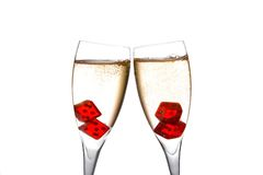 Cheers, red dice in two champagne flutes with gold bubbles Stock Photo