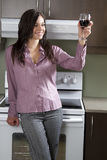 Cheers to that. Young woman standing in front of range appliance, holding a glass a red wine in cheer motion Royalty Free Stock Photography
