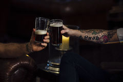Cheers To That. Close up shot of two men toasting their pints stock photo