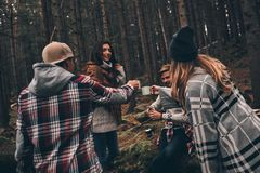 Cheers to friendship! Group of happy young people spending time. Together while hiking in the woods Royalty Free Stock Image