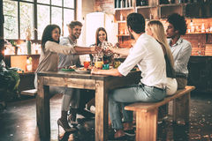 Cheers to us!. Group of cheerful young people cheering with champagne flutes and looking happy while while sitting at the dinning table together Stock Images