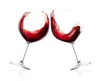 Cheers. A Toast with Red Wine. Splash. Two glasses clicking together over white background. Splashing red wine on balloon glasses stock photos