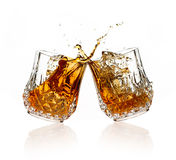 Cheers. A Toast with Whiskey. Two glasses clicking together over white background. Splashing whisky on glasses of cut glass stock image