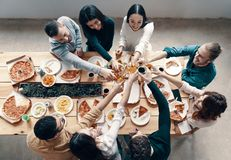 Cheers!. Top view of young people in casual wear toasting each other and smiling while having a dinner party indoors stock image