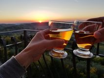 Cheers from Tuscany. A Beer glass cheers and a Tuscan sunset Royalty Free Stock Photo