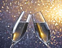 Cheers with two champagne flutes with golden bubbles on light bokeh background. Detail of two champagne flutes with golden bubbles make cheers on light bokeh Royalty Free Stock Photography