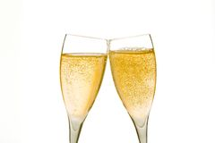 Cheers, two champagne glasses with gold bubbles. On white background Stock Images