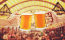 Cheers, two glass beer mugs in hands. On blurred background Stock Images