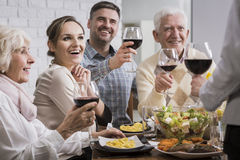 Cheers! For us all!. Happy family during dinner, toasting, holding glasses with red wine Stock Photo