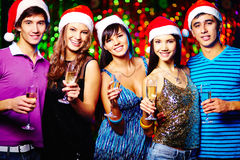 Cheers. Young friends in Santa caps looking at camera while toasting at party stock images