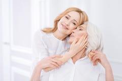 Cheerul verrukte vrouw die haar moeder omhelzen stock foto's