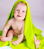 Cheery baby. Covered with a green bath towel Stock Photography