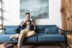 Cheery bearded guy having relax time at his living room Royalty Free Stock Image