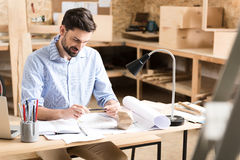 Cheery bearded woodworker thinking over product drafts at his table Royalty Free Stock Image