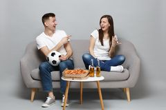 Cheery couple woman man football fans cheer up support favorite team with soccer ball, pointing index fingers isolated. Cheery couple women men football fans royalty free stock photography