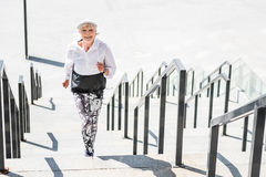 Cheery elderly lady running up concrete steps outdoors Stock Images